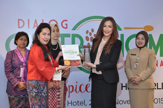 Dian Fatmayanty from Akademi Gastronomi Indonesia is presenting the award to Debby Setiawaty as Director of Public Relations for the Hotel Gran Mahakam
